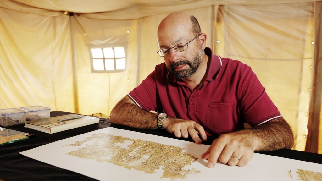 Pierre Tallet taking a closer look at the papyri fragments found at Wadi al-Jarf